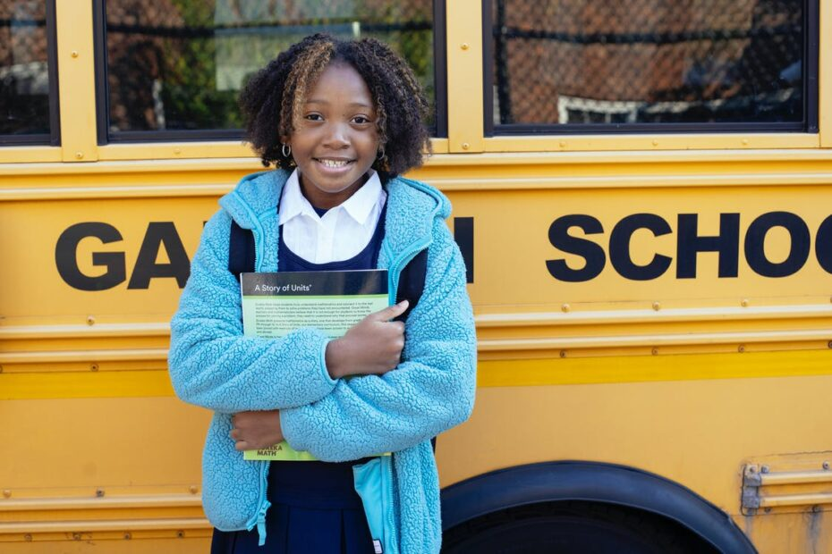 a black child in front of a school bus - the impoortance of FM to the nigerian child